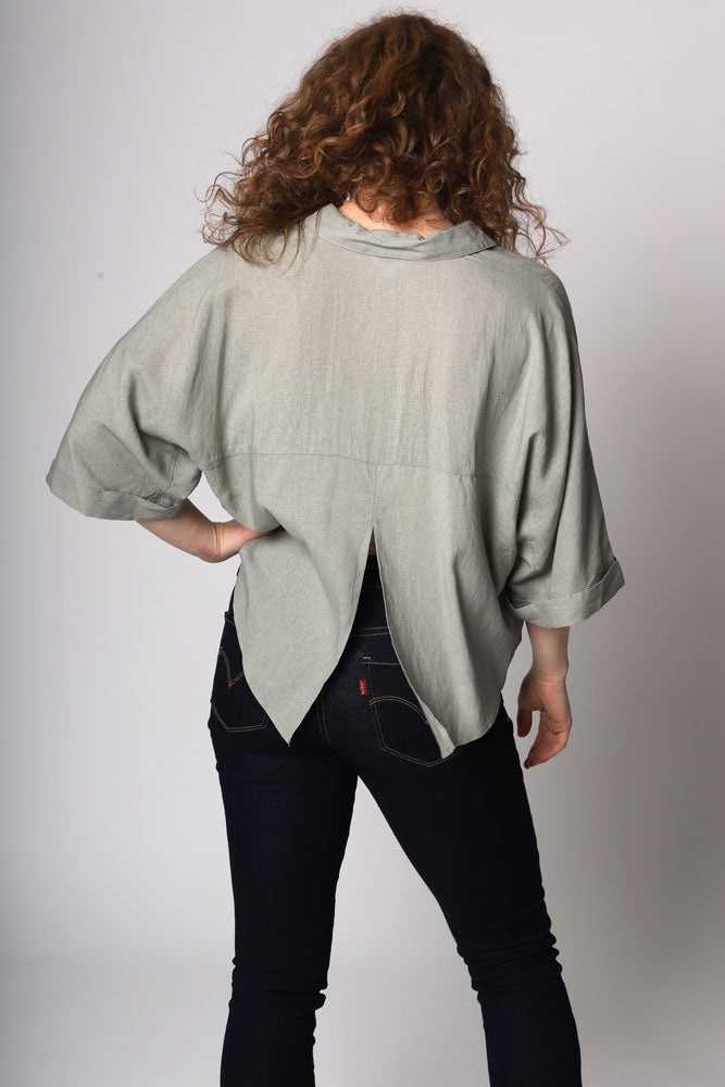 The Let's Split top is a linen blend dolman sleeve shirt with a button front and split back detail.