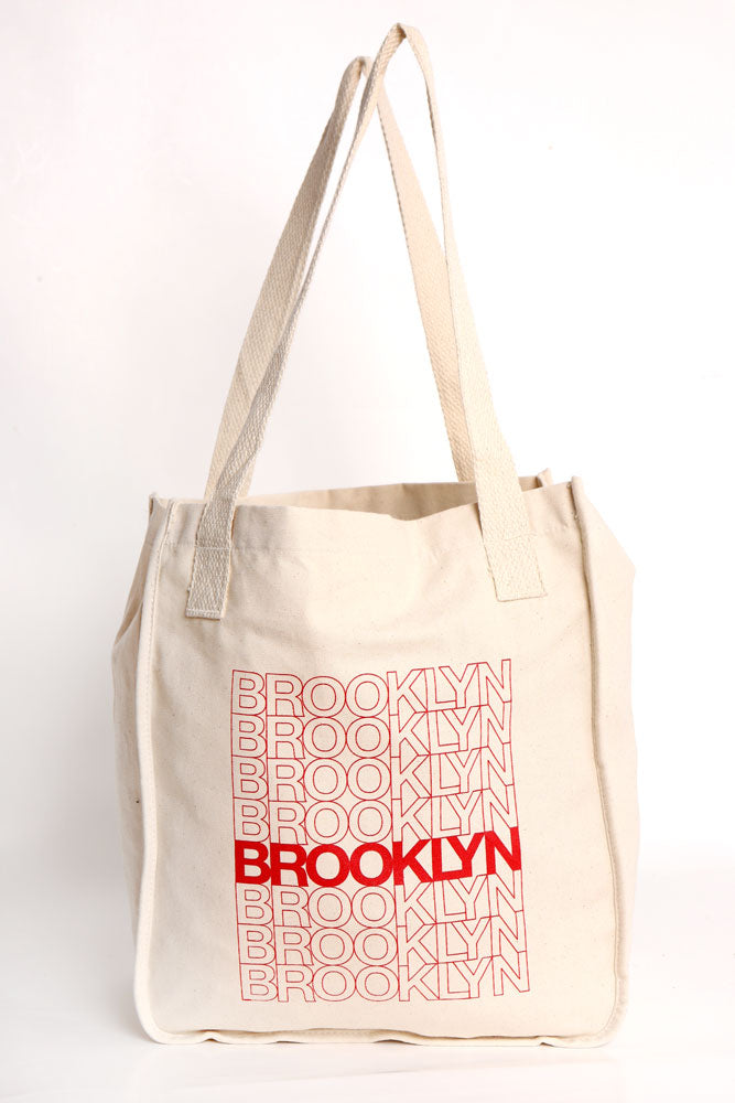 ORGANIC COTTON TOTE BAG WITH BROOKLYN TEXT DOWN THE FRONT LIKE A CLASSIC BODEGA BAG - NATURAL TOTE BAG COLOR, WITH RED TEXT GRAPHIC