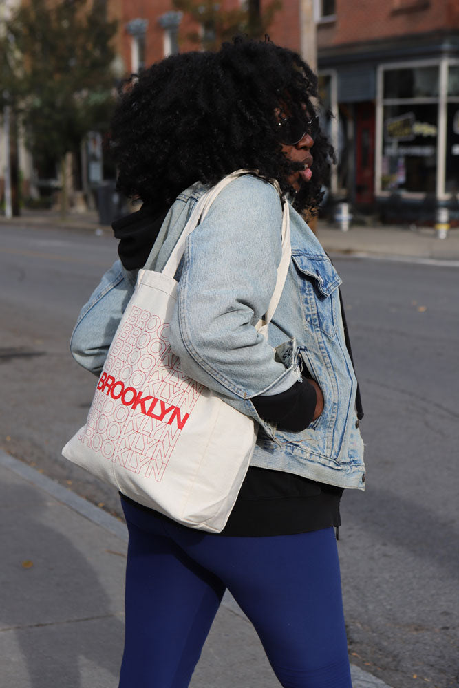 WOMEN CROSSES STREET IN JEAN JACKET AND LINEN THANK TOTE BY BROOKLYN INDUSTRIES
