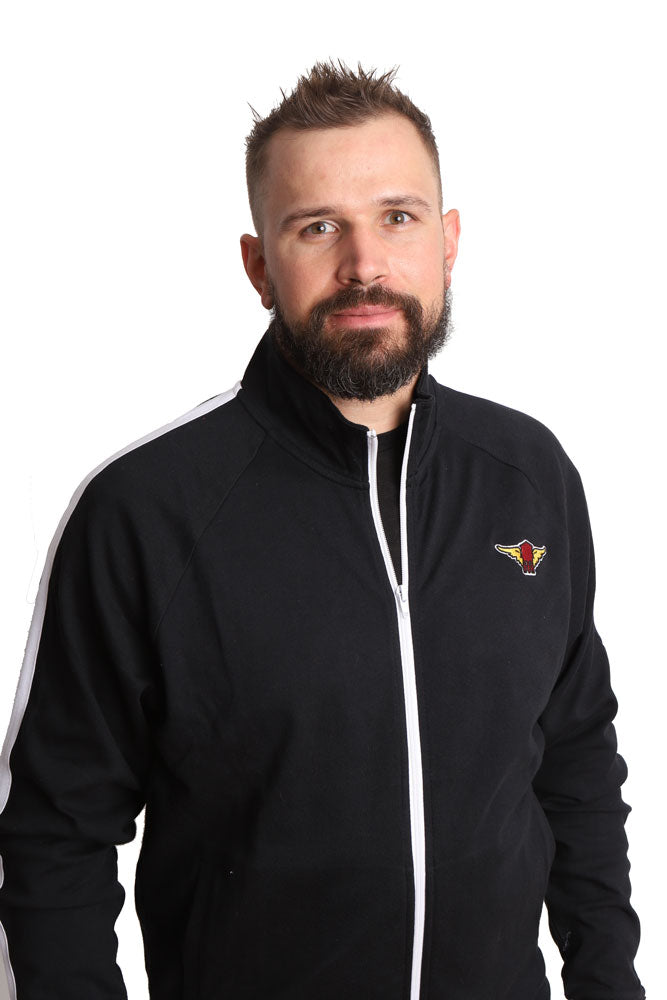 man with beard looks at camera wearing black track jacket with white piping, half unzipped, with winged water tower patch on left chest