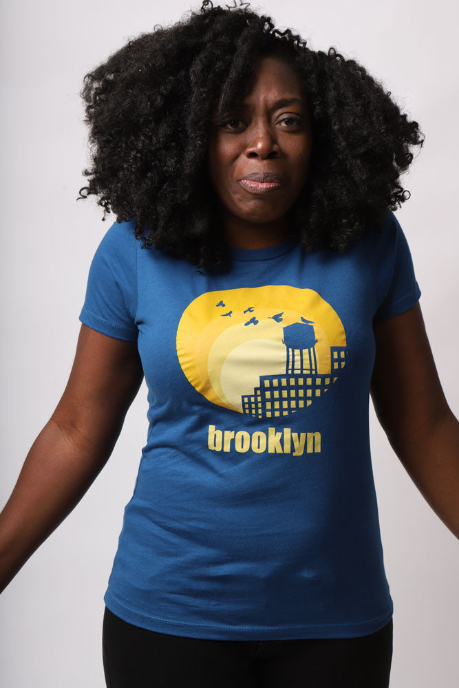 women with afro shrugs at camera wearing blue water tower sun shirt