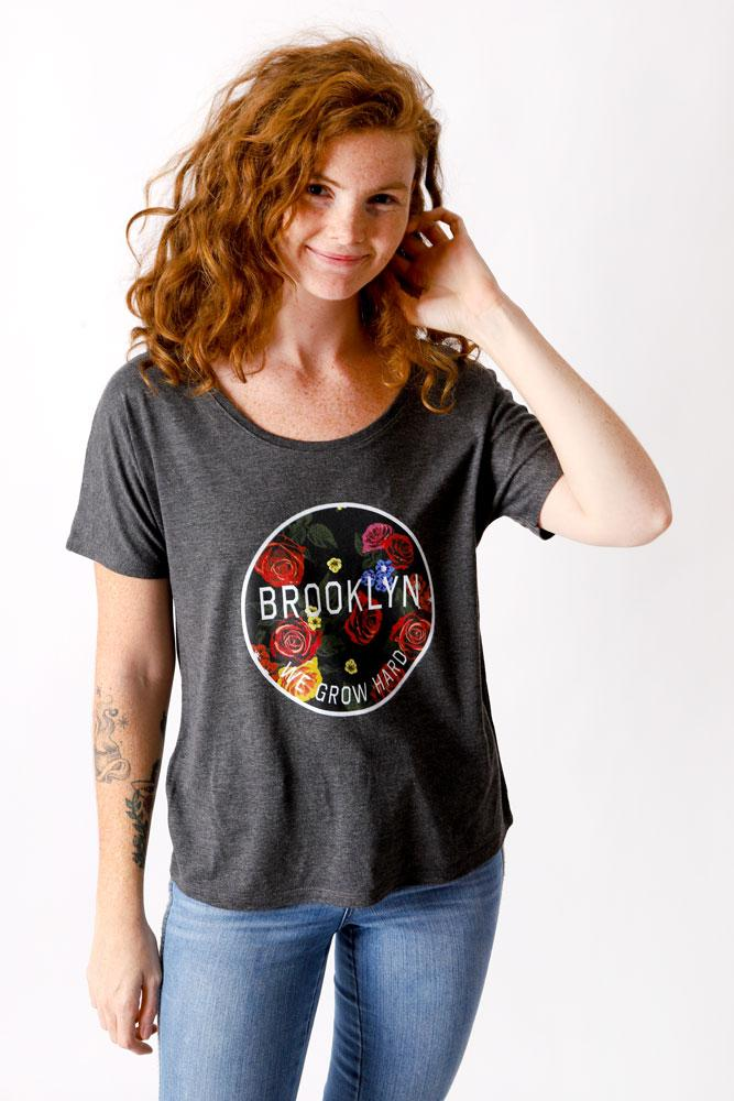 Women with red curly hair looks shyly at the camera, wearing charcoal we grow hard women's wide neck t-shirt