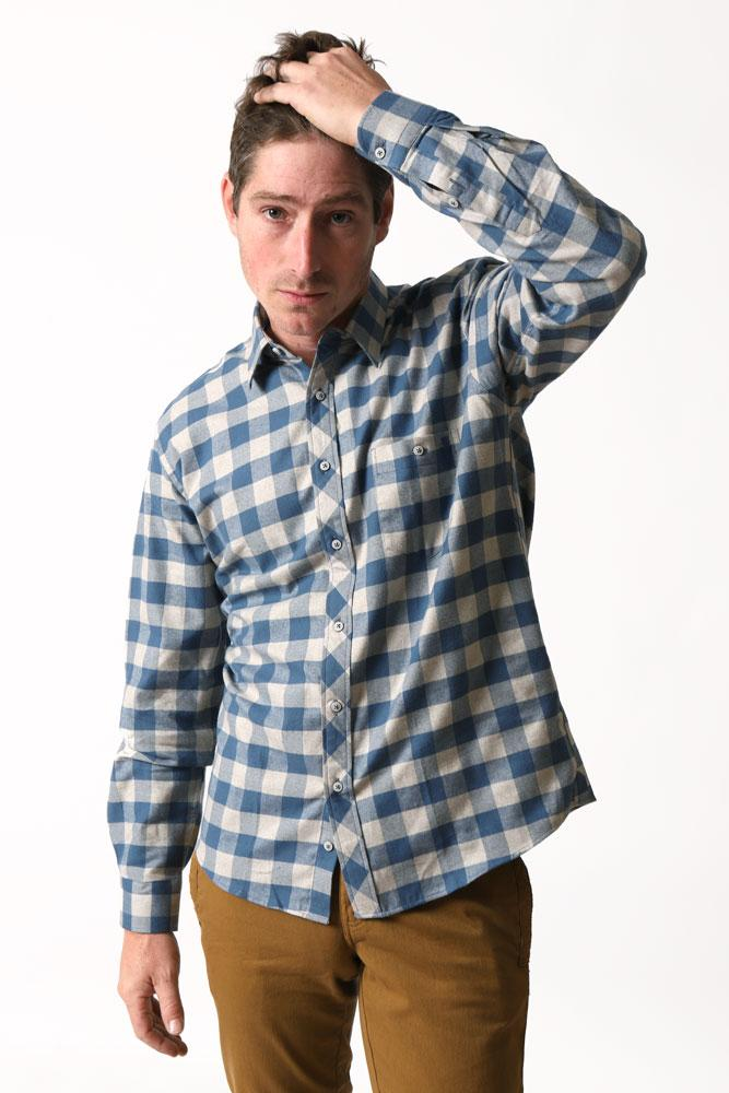 man tugs on hair in toast pants, and a blue and tan check flannel long sleeve woven shirt