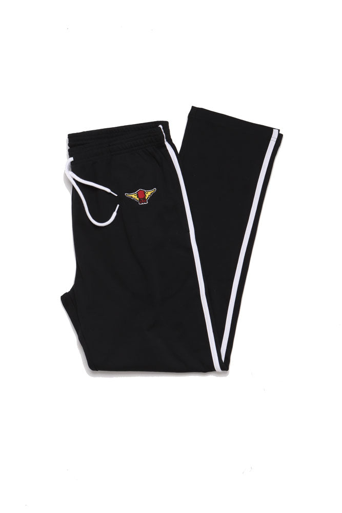 flat lay of black track pant with white piping, folded in half showing the patch on the hip