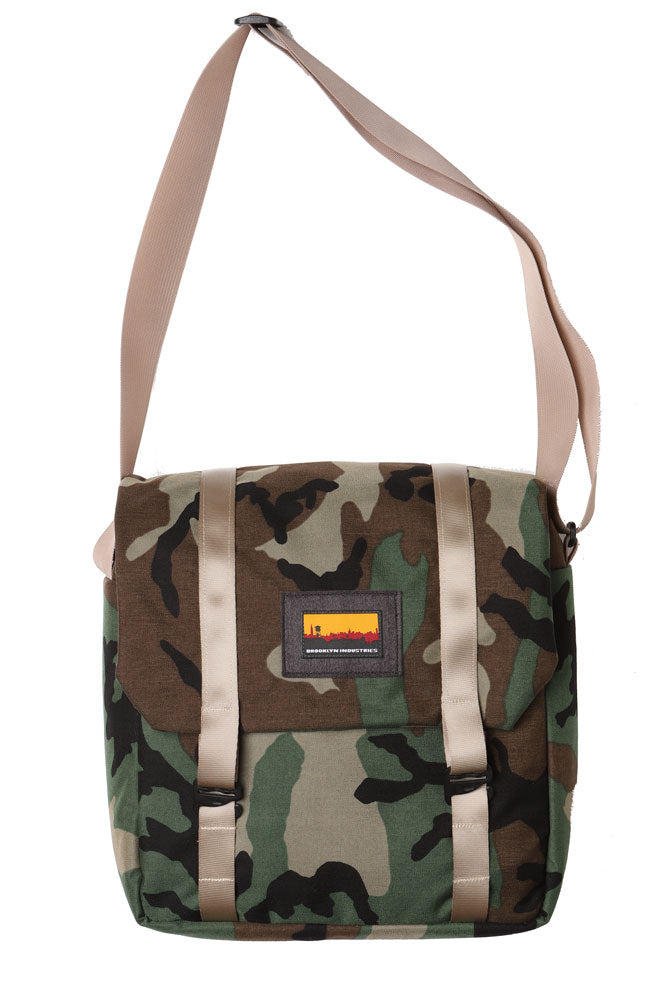 cross body style bag with a flip top and khaki webbing straps. flat lay image of the mail bag in woodland camo