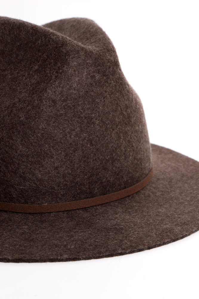 detail of brown wool hat with brown faux leather strapping detail