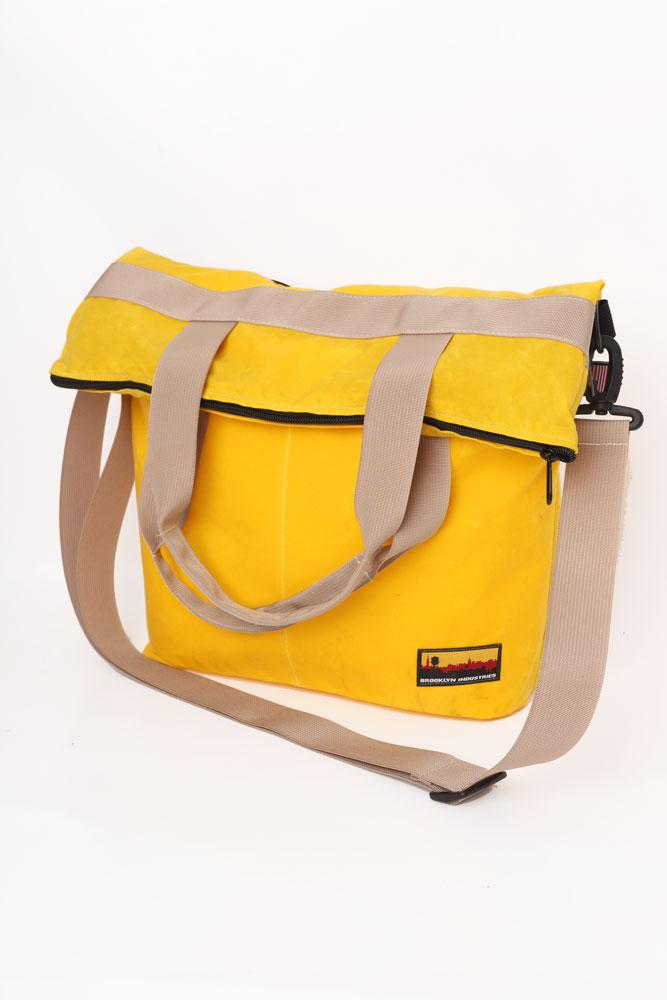SIDE VIEW OF WAXED CANVAS ZIP MESSENGER BAG IN YELLOW