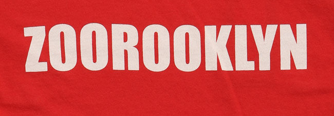 detail of the text ZOOROOKLYN across the chest in white on red youth shirt