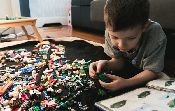 Boy playing with legos in room