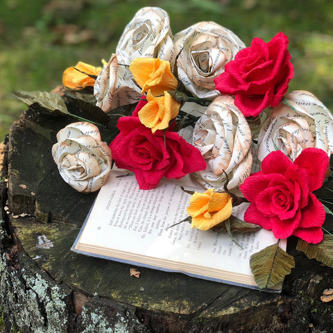 paper flowers on a tree stump with a book