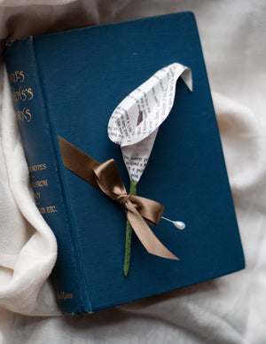 book page calla lily paper boutonniere buttonhole sitting on a book