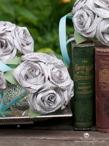 wedding bouquets made out of book pages sitting with some books