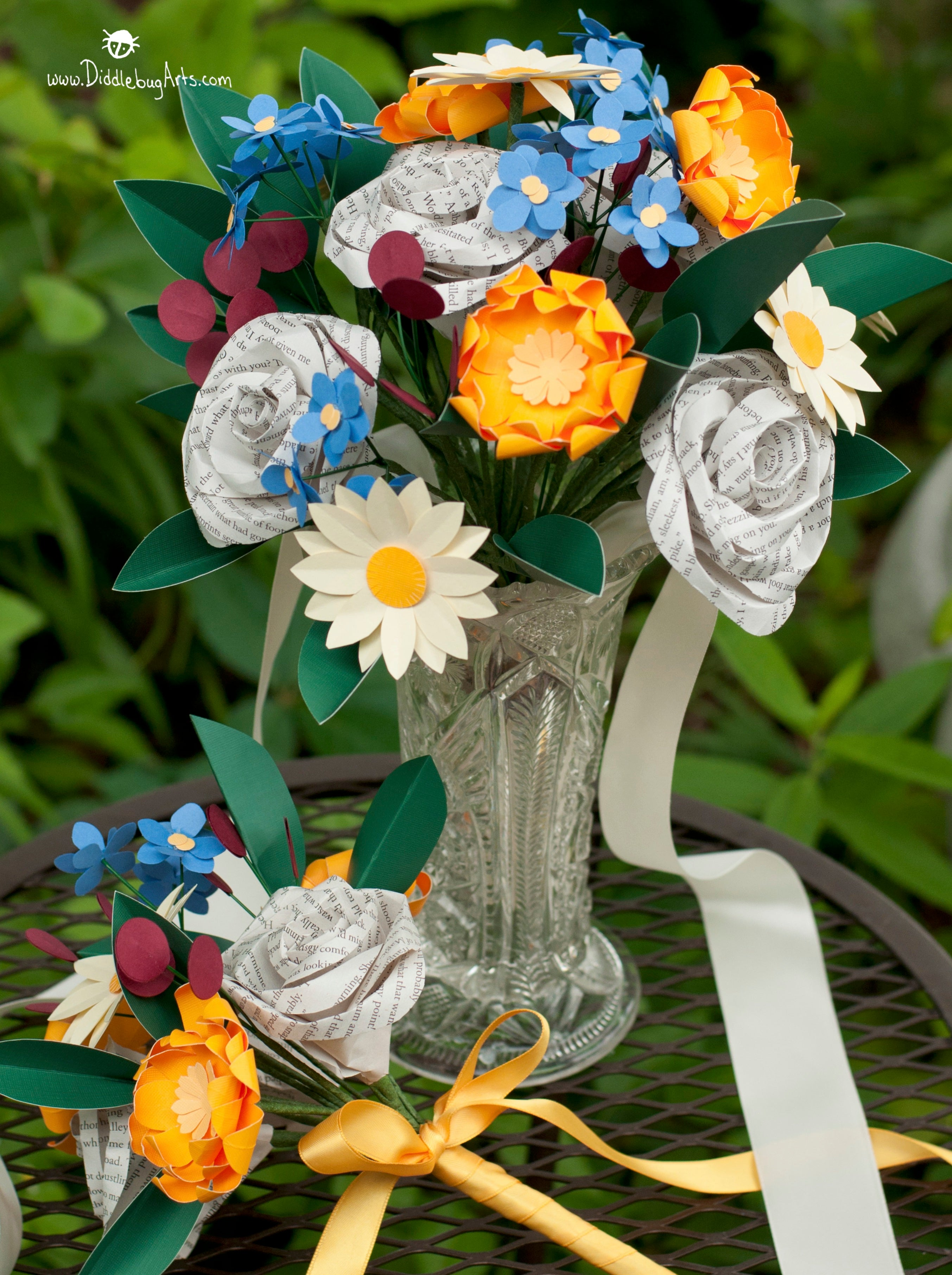 Bridal bouquet in a vase made of paper book page and colored flowers and a matching bridesmaid bouquet sitting next to  the vase