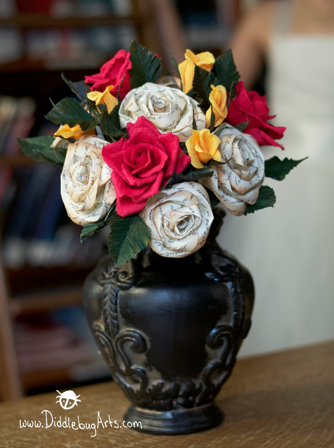 beauty and the beast inspired paper rose bouquet in a vase in a library