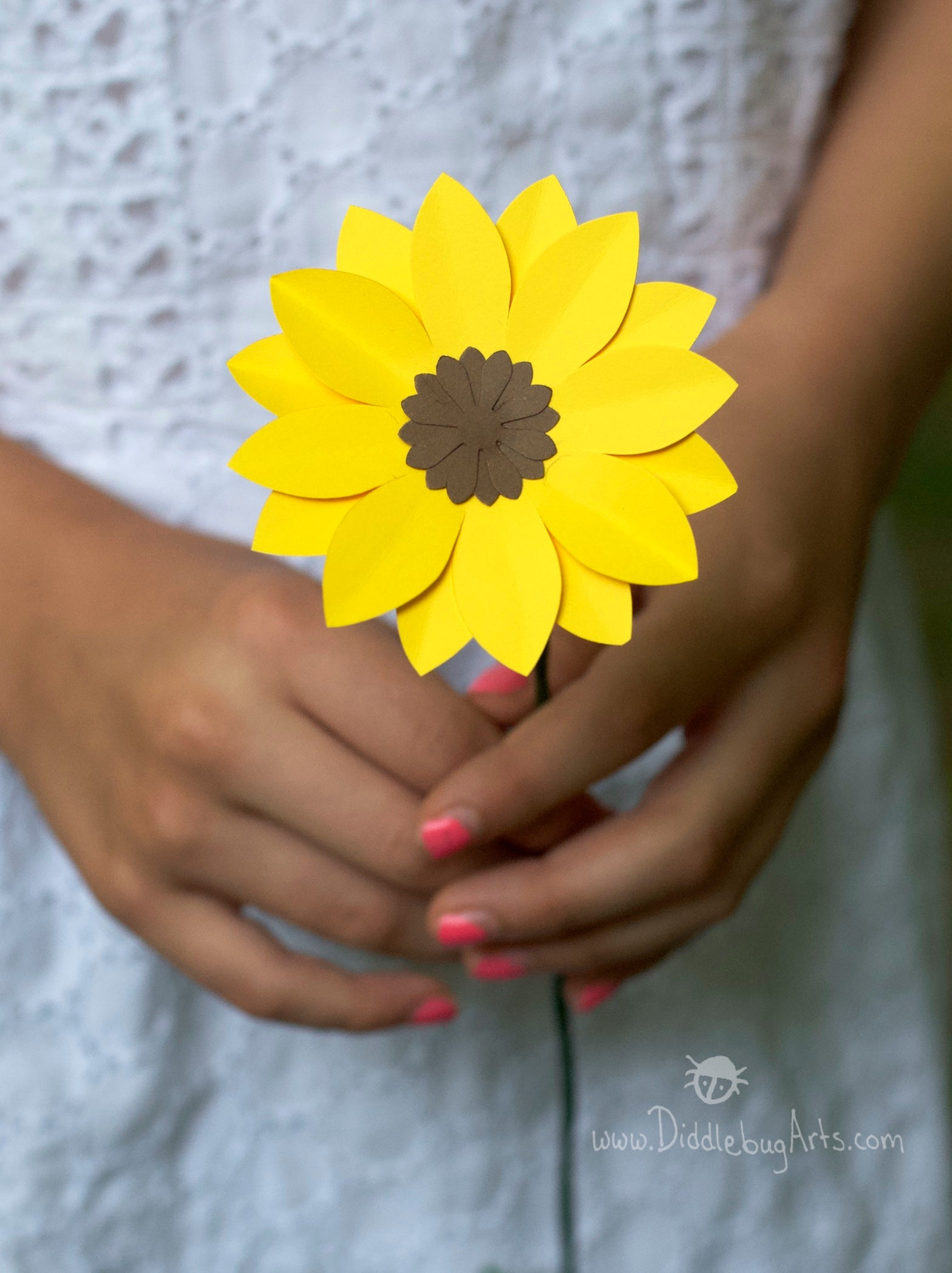 single paper yellow black-eyed susan daisy flower being held by a young girl