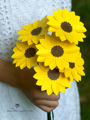 paper bouquet of yellow black-eyed susans being held by a girl