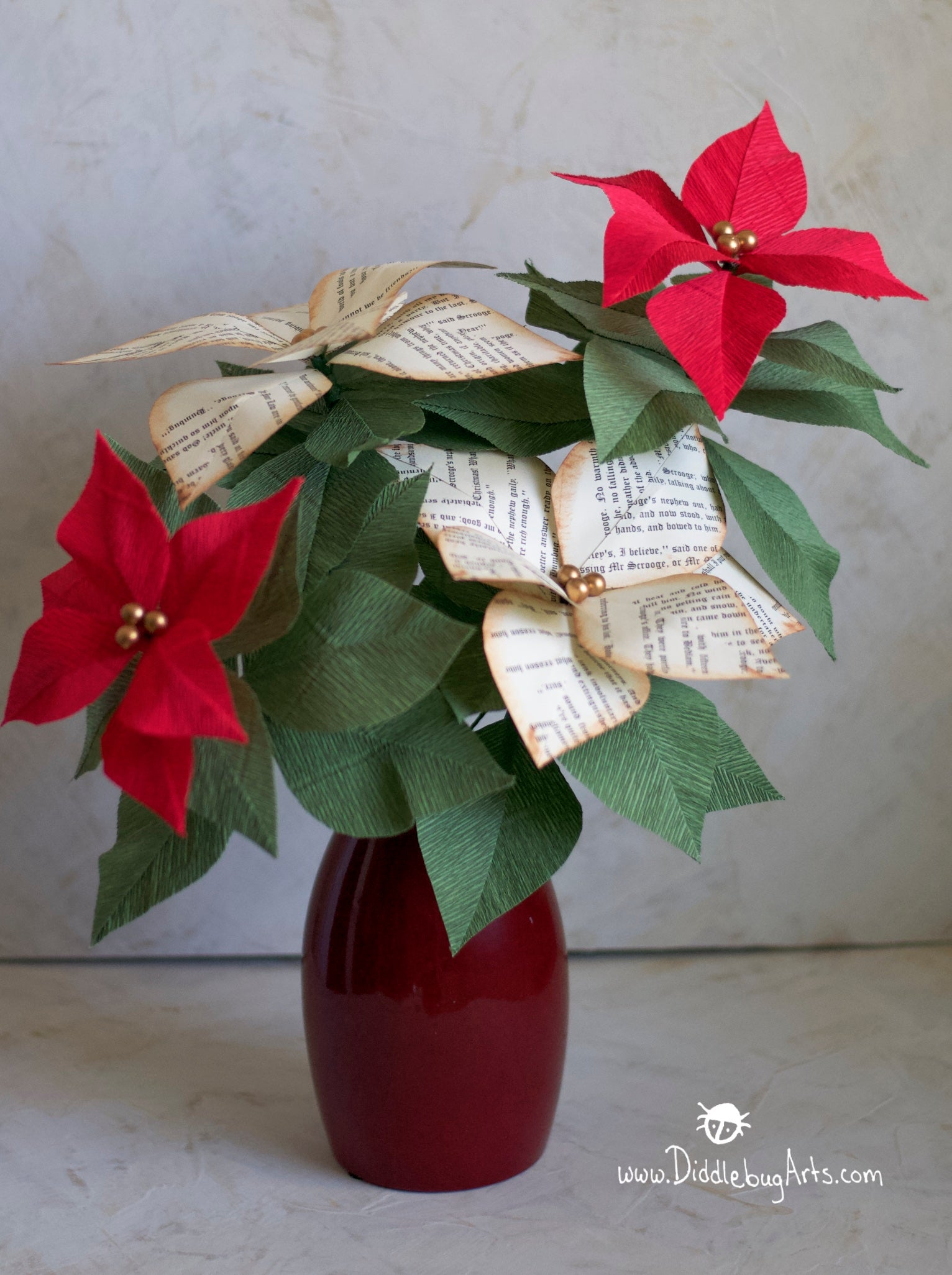 red crepe paper poinsettia plant with some book page poinsettias