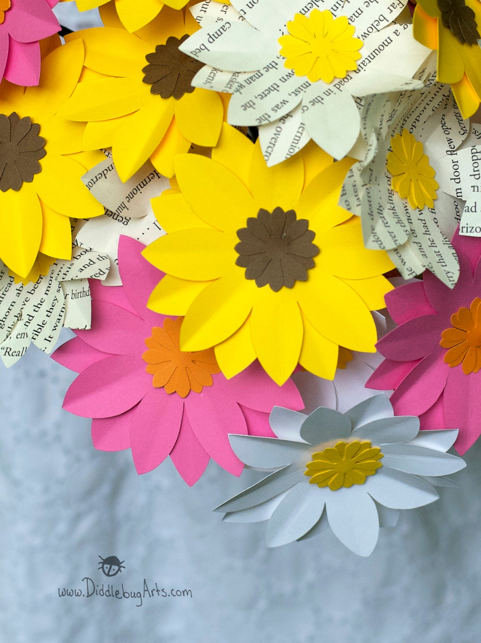 close up of mixed color daisies made of paper and book pages