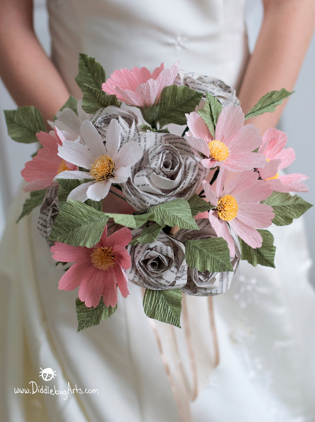 bride holding a paper cosmos and book page bouquet
