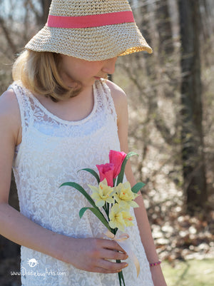 young girl with a paper daffodil and tulip spring bouquet