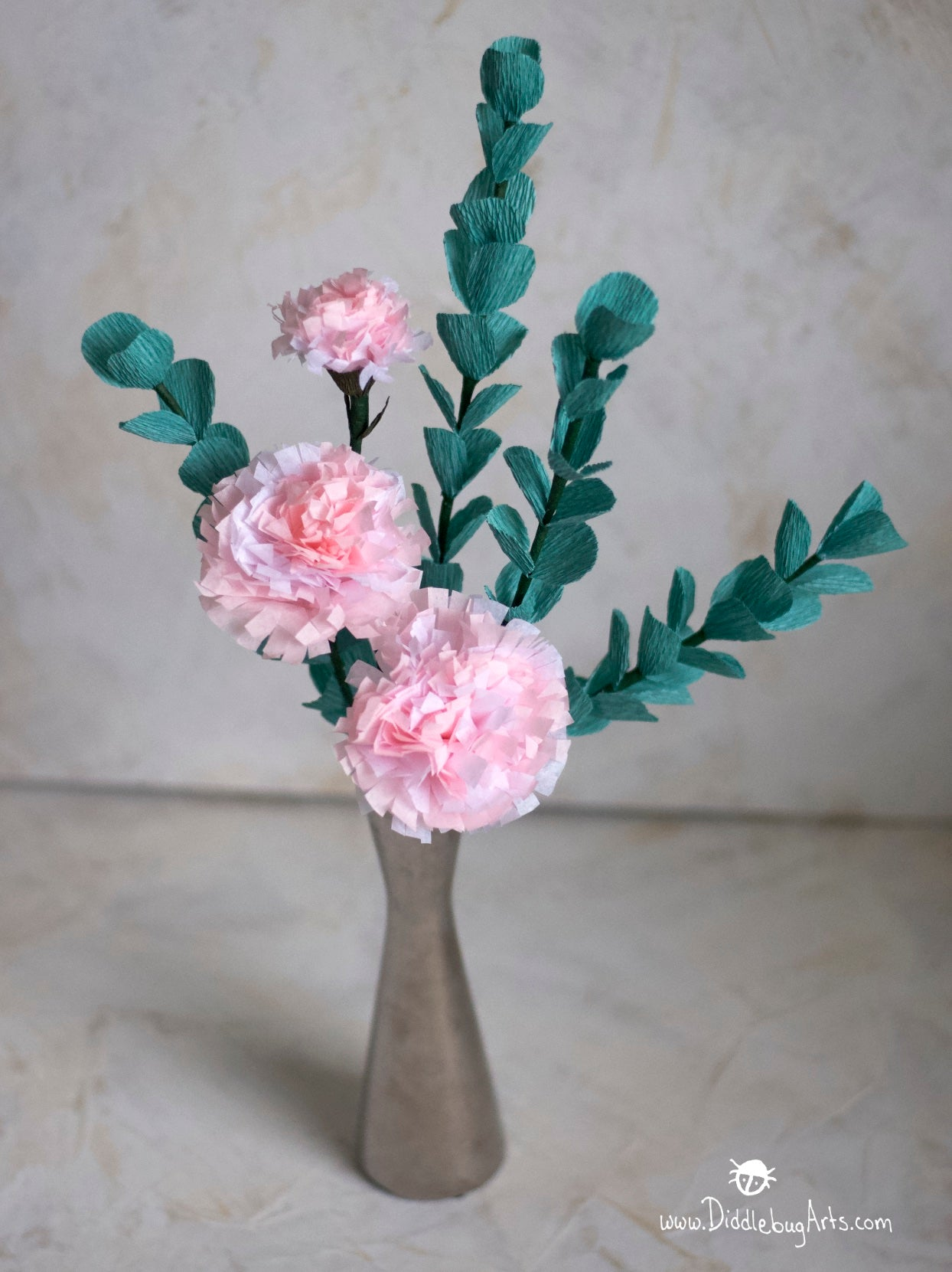 Paper eucalyptus stems in a silver vase with paper pink carnations