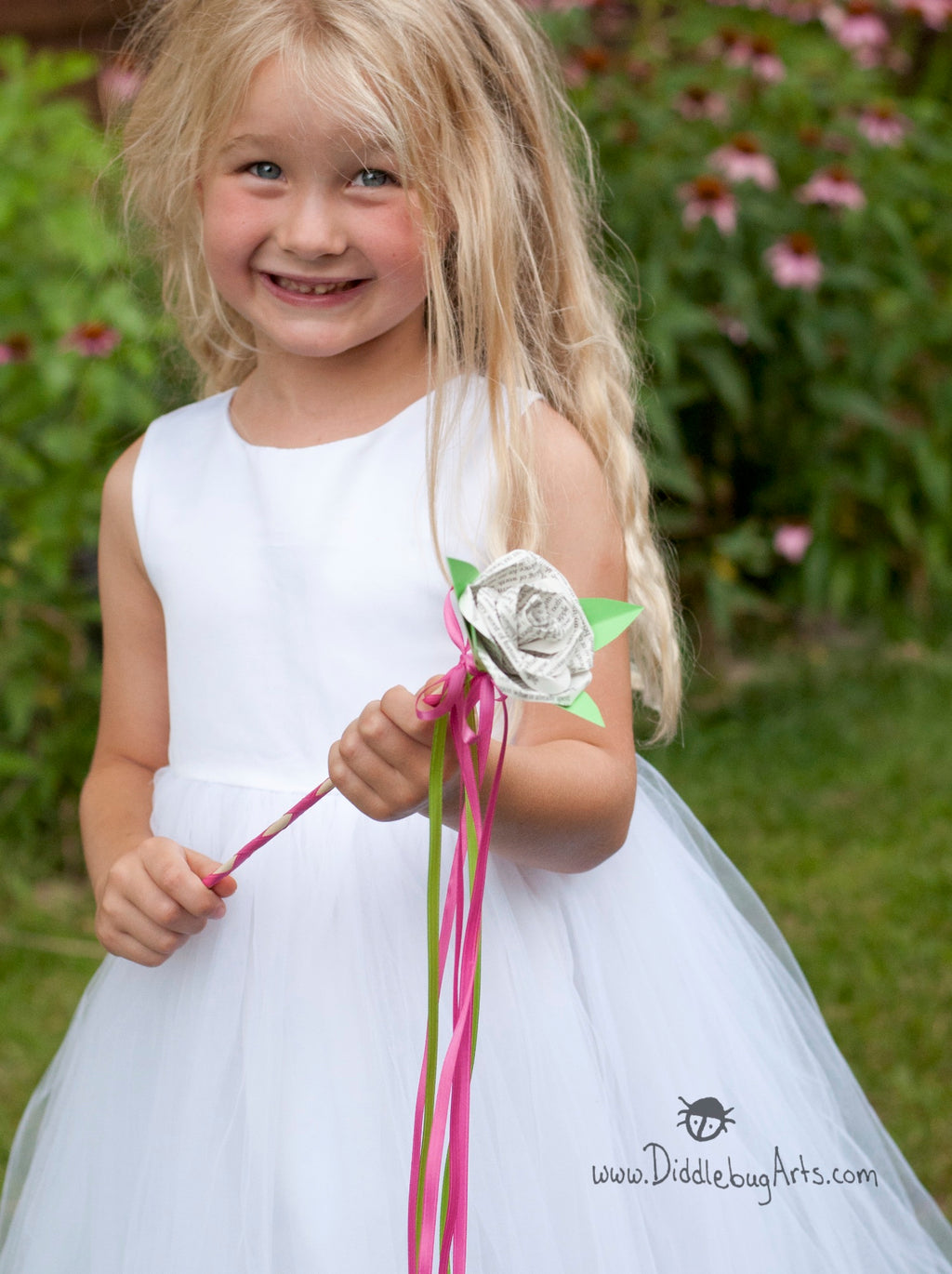 young girl holding a flower girl wedding wand with streamers and a paper book page rose on the end