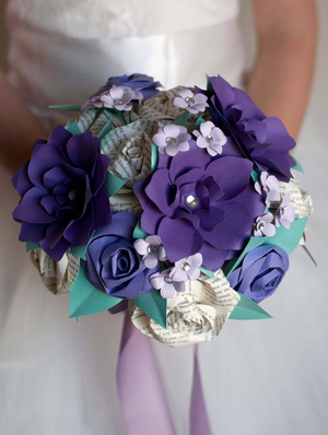 purple gardenias and book page roses in a wedding bouquet held by a girl