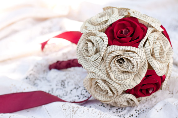 wedding bouquet sitting on lace with red velvet roses and book page paper roses