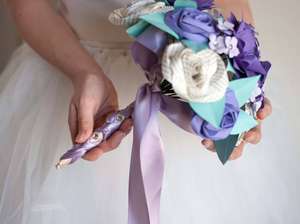 side view of bridal bouquet made of paper with book page roses and purple roses and gardenias
