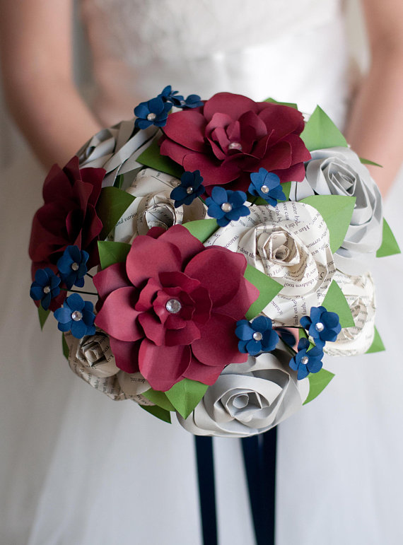 dark red gardenias, small blue flowers and book page roses in a wedding bouquet