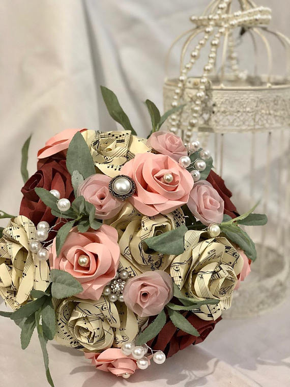 Paper rose and pearl wedding bouquet sitting next to a bird cage