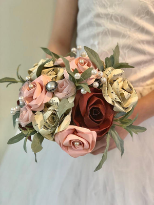 paper rose and pearl bridal bouquet being held by a girl
