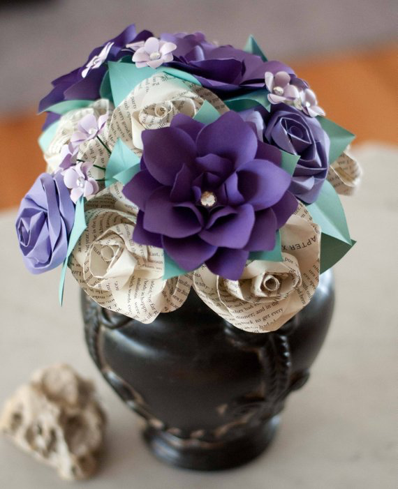 Purple gardenias and book page roses in a bridal bouquet in a vase