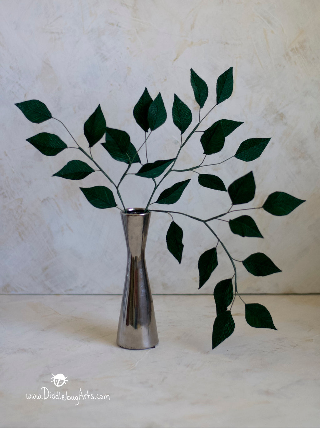 crepe paper leafy branches in a silver vase