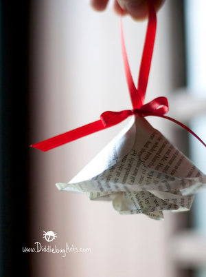Paper book page ornament on a red ribbon