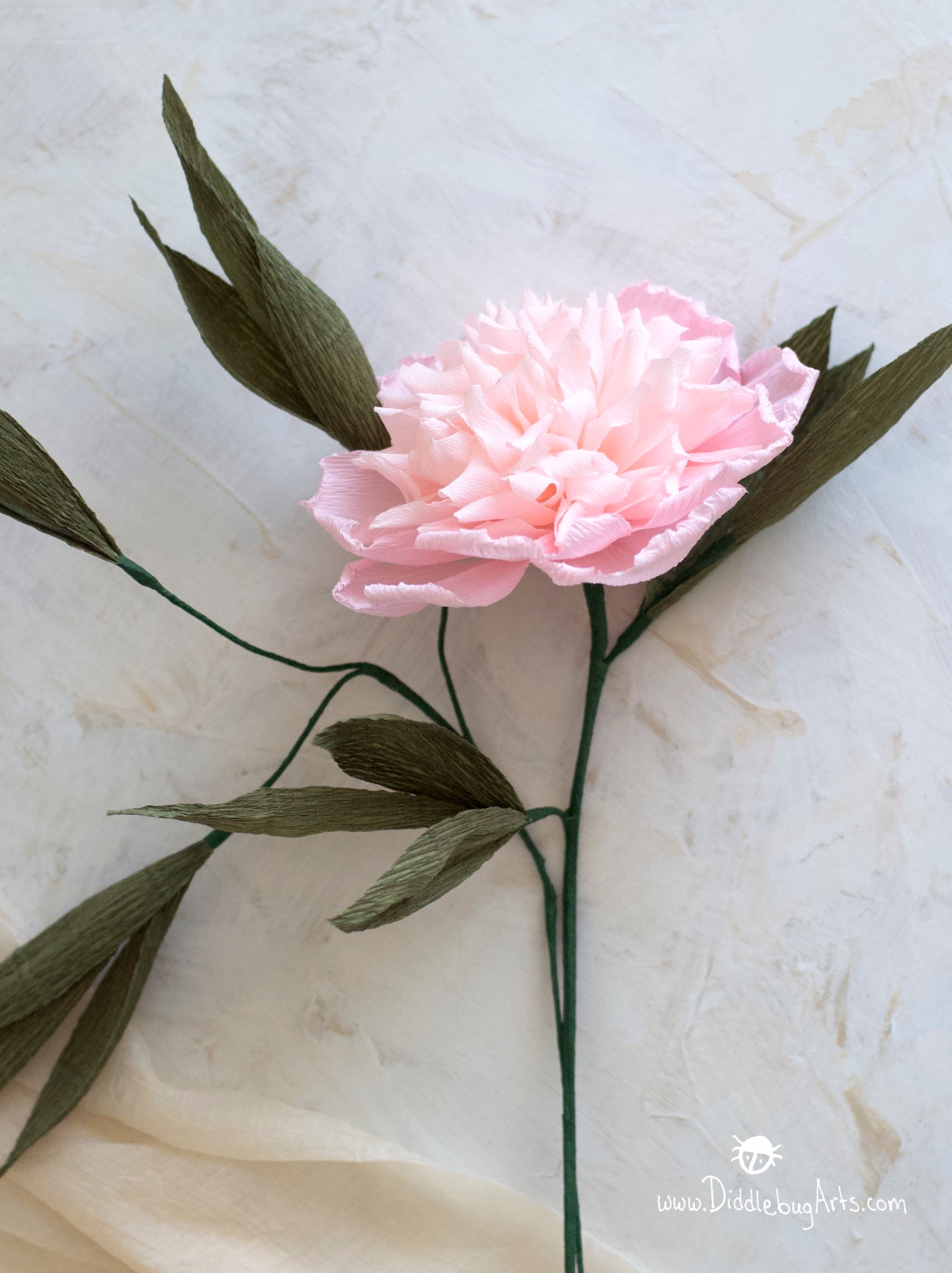 pink crepe paper peony with extra leaves
