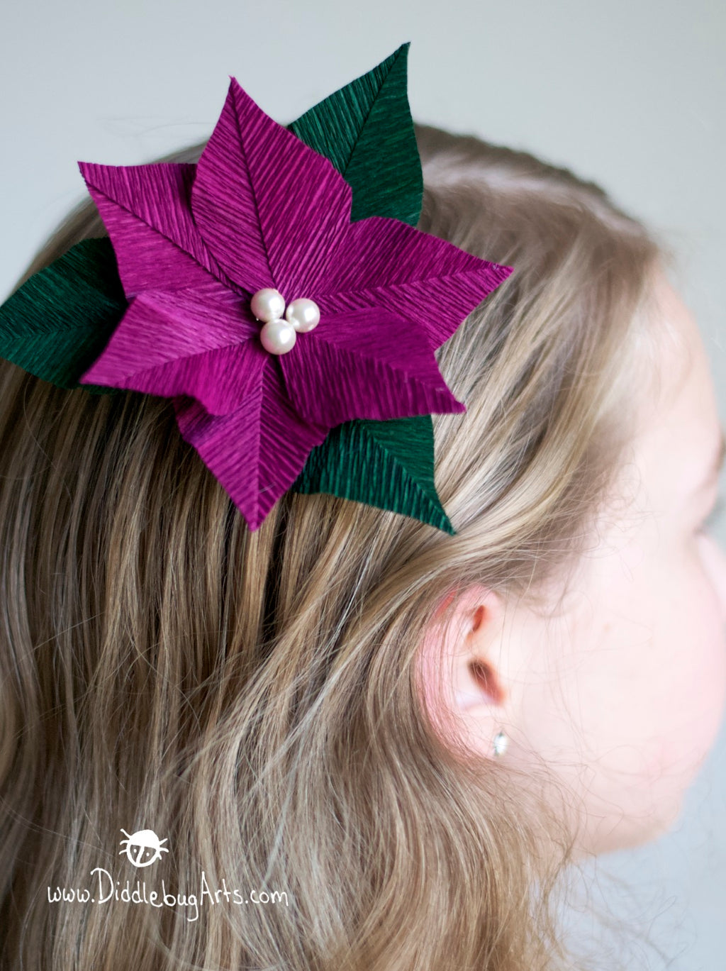girl with a dark pink crepe paper poinsettia pin in her hair