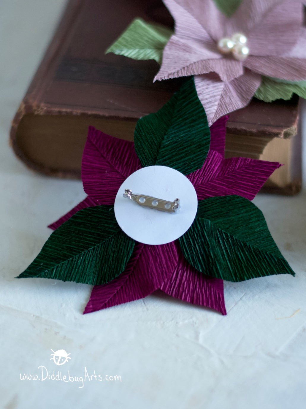 showing the back of a small crepe paper poinsettia pin broach