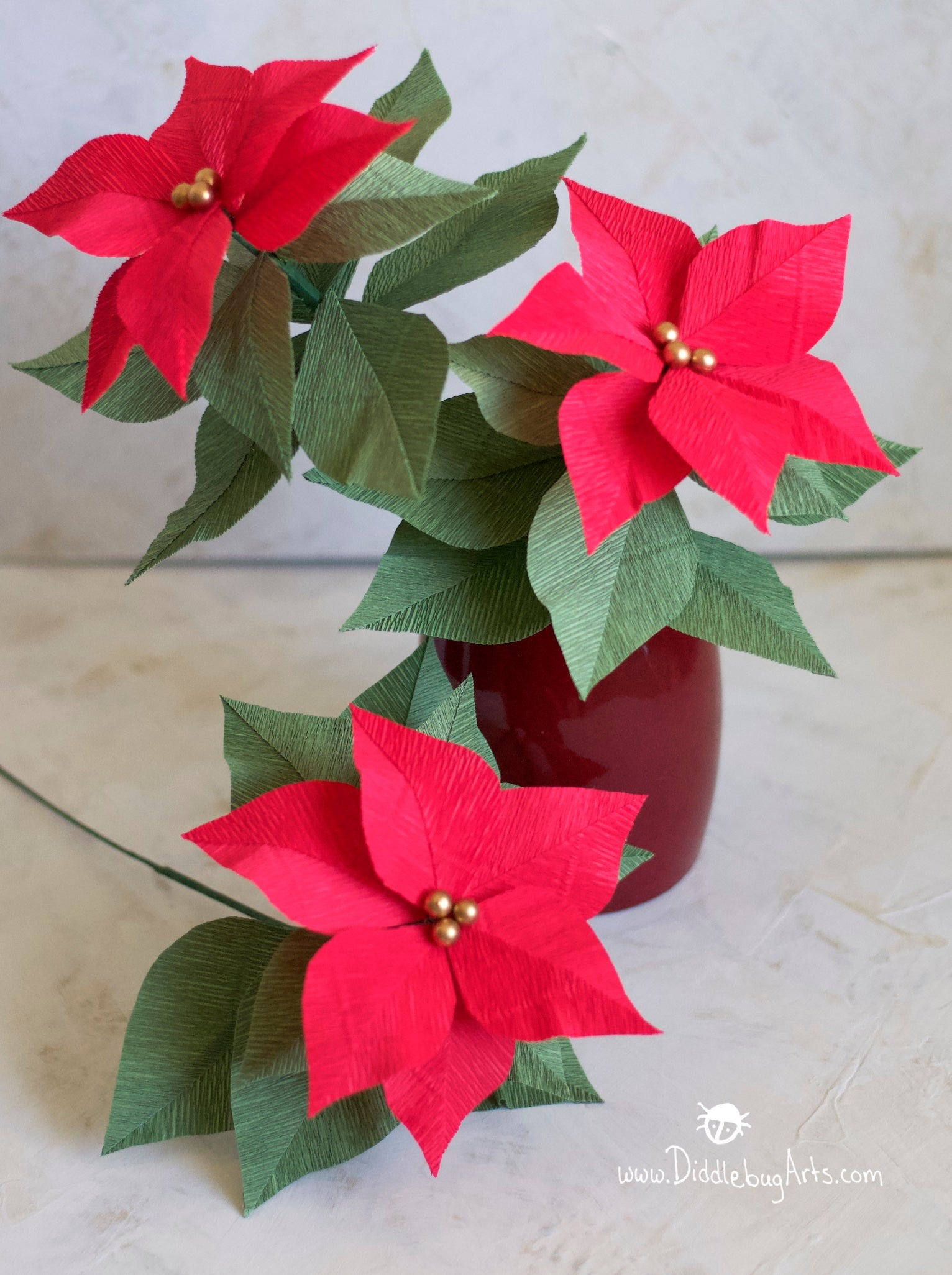 vase with red poinsettia plant made of crepe paper