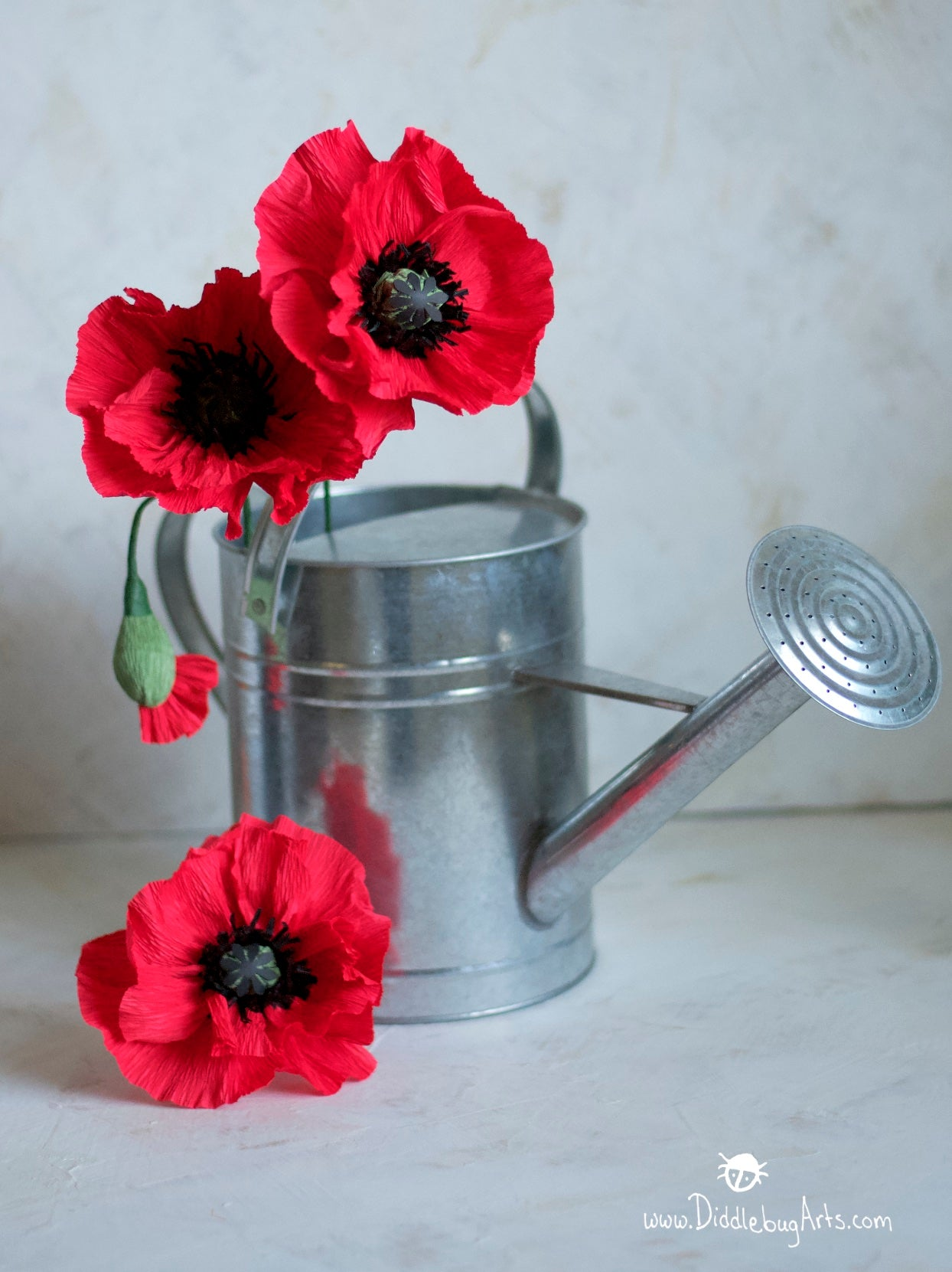 red crepe paper poppies in a watering can