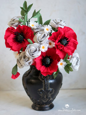 red crepe paper poppies and paper book page roses in a vase