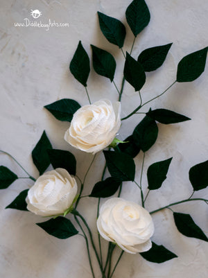 three cream crepe paper ranunculus flowers with paper greenery