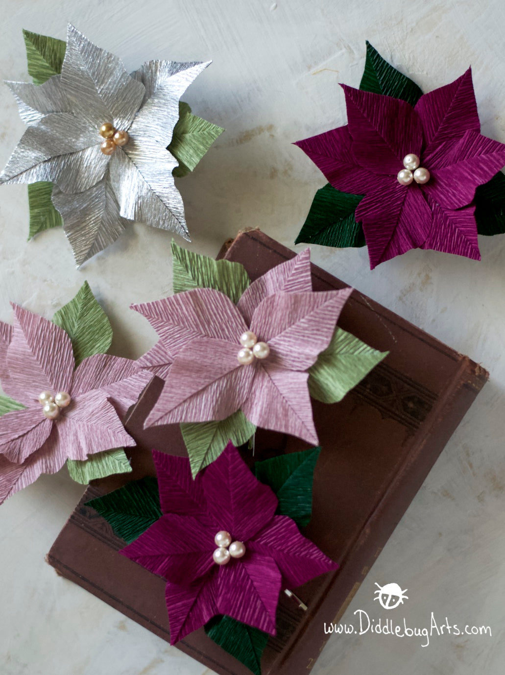 several tiny crepe paper poinsettia flowers hair pins