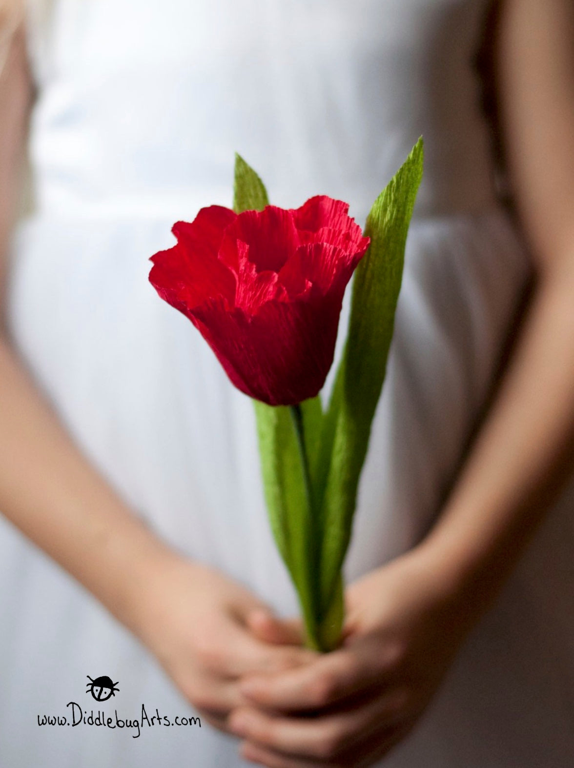red crepe paper tulip held by a young girl