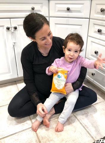 Woman with daughter eating Puffworks baby peanut butter puffs