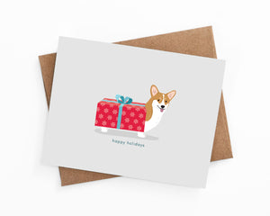 Illustrated happy holiday corgi wrapped in a present card by LaCorgi.