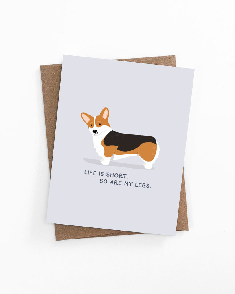 "Illustrated greeting card of a tricolor corgi with text ""Life is short. So are my legs."" by LaCorgi."