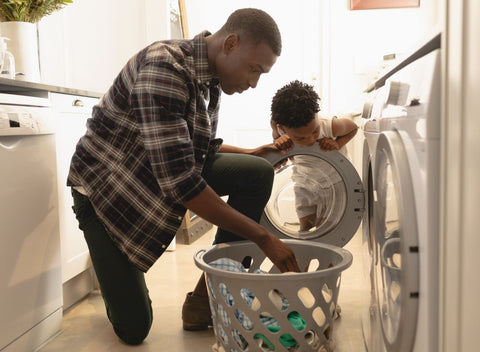 father and son pulling laundry out of the washing machine