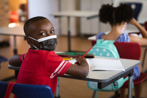 Child sitting at a desk in school while wearing a face mask