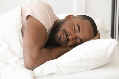 Man sleeping well using essential oils and a weighted blanket